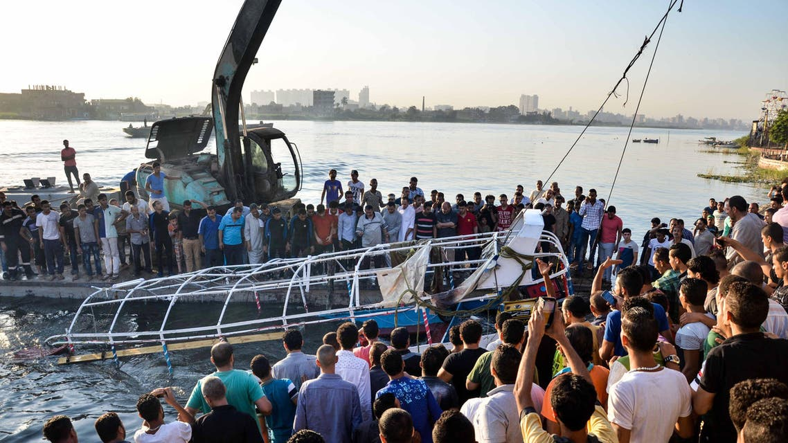 Egyptians look at the passenger boat that sunk in the river Nile in Giza, south of Cairo, Egypt, Thursday, July 23, 2015. AP