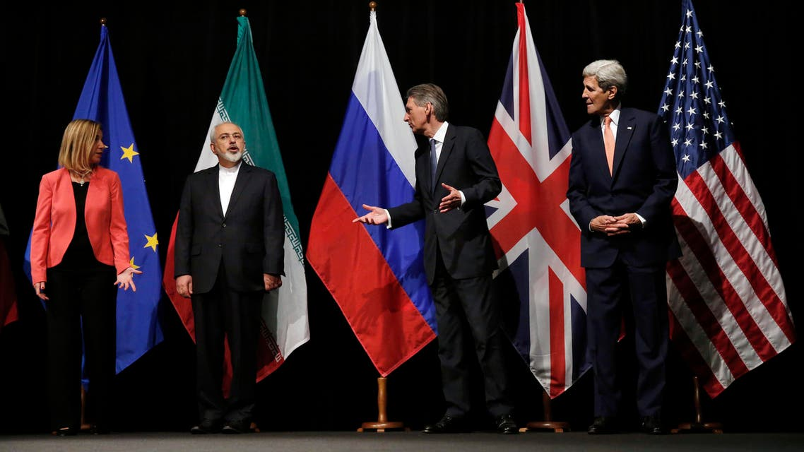 British Foreign Secretary Philip Hammond, 2nd right, U.S. Secretary of State John Kerry, right, and European Union High Representative for Foreign Affairs and Security Policy Federica Mogherini, left, talk to Iranian Foreign Minister Mohammad Javad Zarif as the wait for Russian Foreign Minister Sergey Lavrov, not pictured, for a group picture at the Vienna International Center in Vienna, Austria, Tuesday, July 14, 2015. After 18 days of intense and often fractious negotiation, world powers and Iran struck a landmark deal Tuesday to curb Iran's nuclear program in exchange for billions of dollars in relief from international sanctions — an agreement designed to avert the threat of a nuclear-armed Iran and another U.S. military intervention in the Muslim world. (Carlos Barria, Pool Photo via AP)