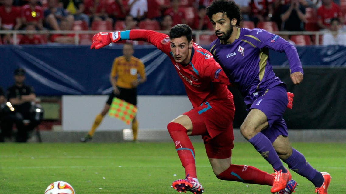 Fiorentina's Mohamed Salah, right, challenges Sevilla goalkeeper Sergio Rico during the Europa League semifinal, first leg, soccer match between Sevilla FC and Fiorentina at the Ramon Sanchez Pizjuan stadium in Seville, Spain, Thursday, May 7, 2015.