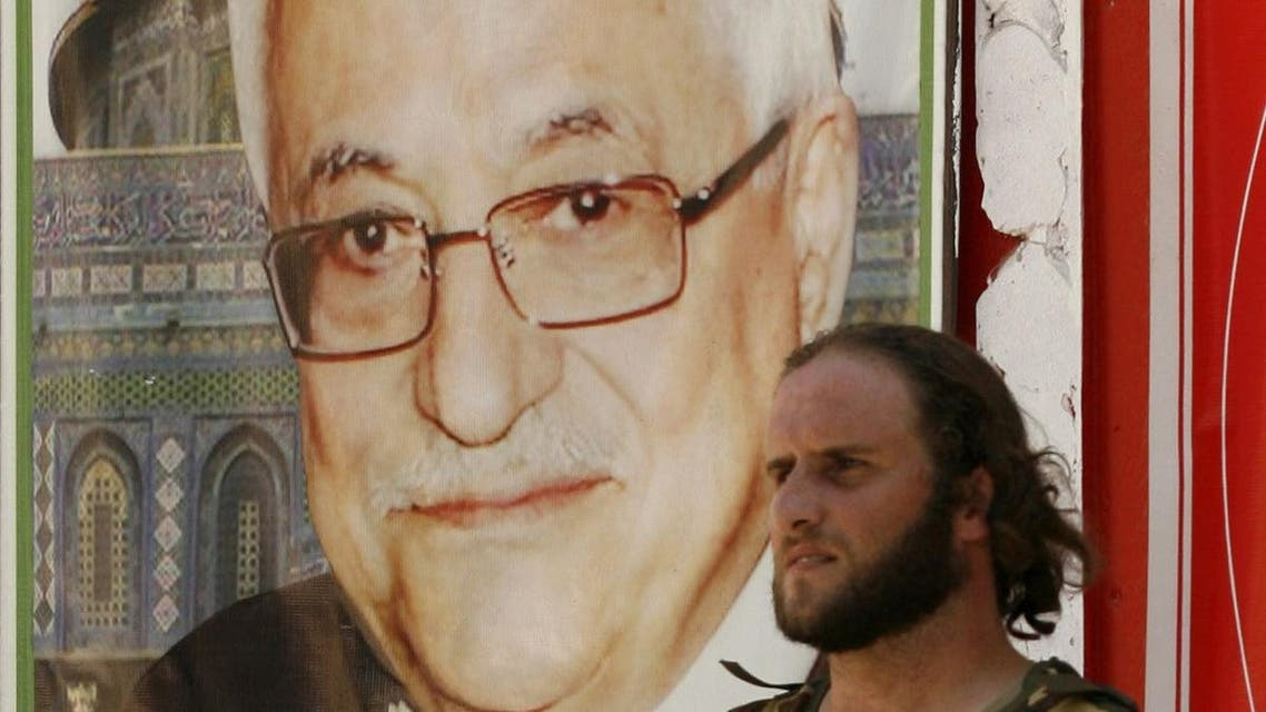 MZ01 - Ain El-Helweh, -, LEBANON : An armed man stands next to a poster bearing the portrait of Palestinian president Mahmud Abbas on July 25, 2015, in Lebanon's southern Palestinian refugee camp of Ain El-Helweh, after Talal al-Ourdouni, a senior member of Abbas' Fatah movement, was shot dead in the camp. AFP PHOTO / MAHMOUD ZAYYAT