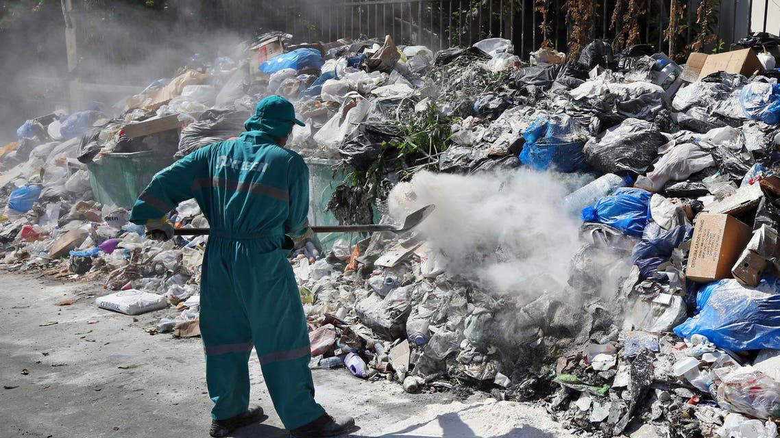 A waste management worker covers a pile of garbage using white pesticide in the Palestinian refugee camp of Sabra in Beirut, Lebanon, Friday, July 24, 2015.