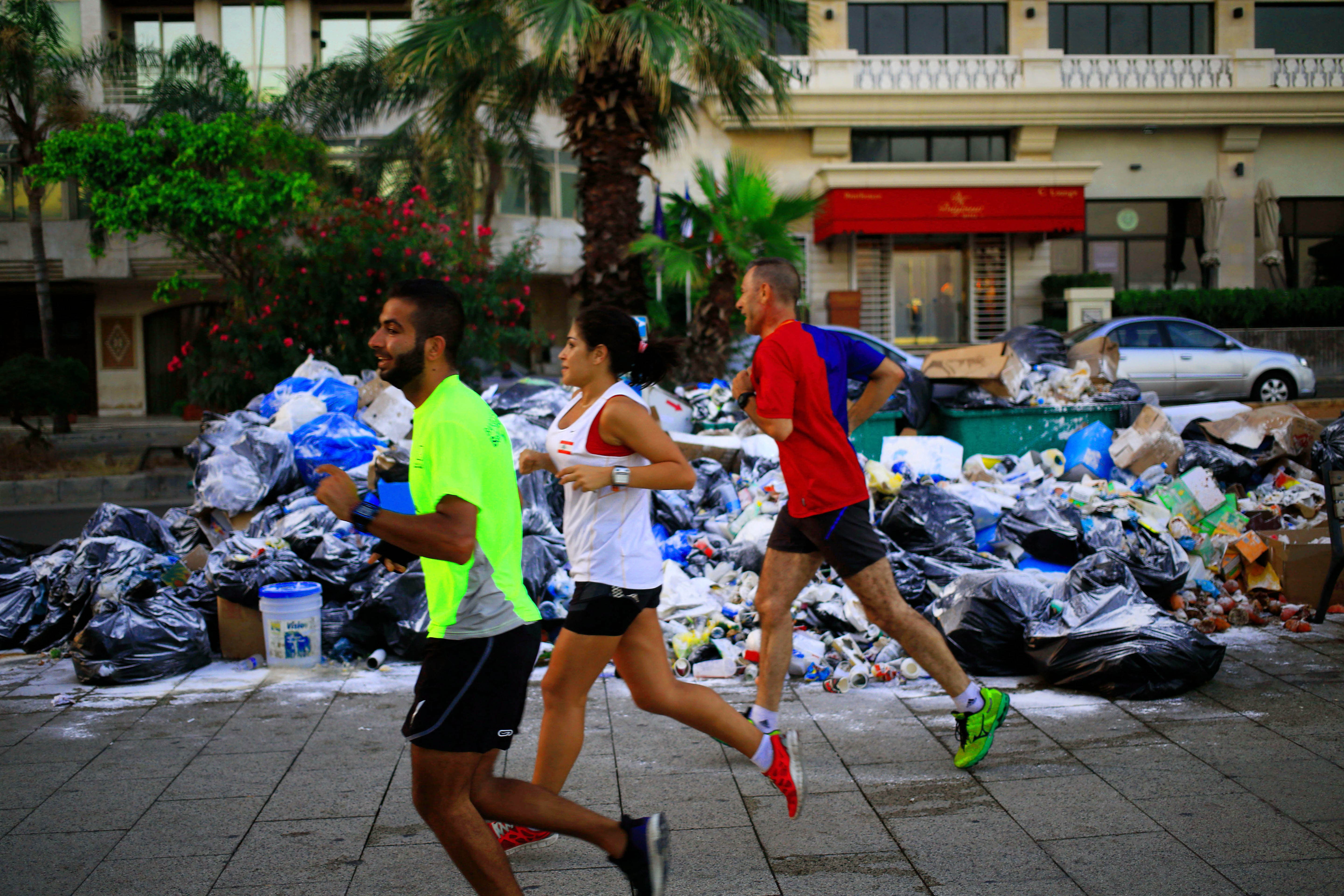 Lebanese run by loads of garbage on the Beirut coastline, Lebanon, Tuesday, July 21, 2015.