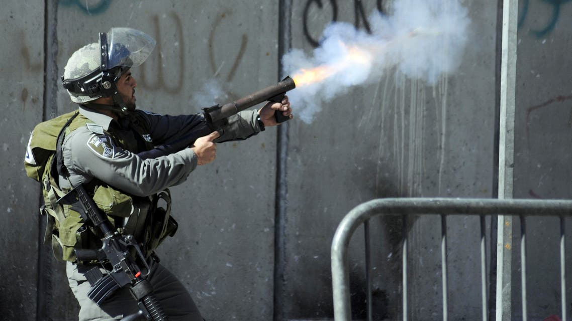 Israeli border policeman shoots tear gas during clashes with Palestinians, as Israeli police limited the access to Al-Aqsa Mosque, in Jerusalem on Friday, Nov. 7, 2014. AP