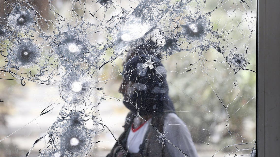 Southern Resistance fighter is pictured through a damaged door glass as he stands guard at the international airport of Yemen's southern port city of Aden. (Reuters)