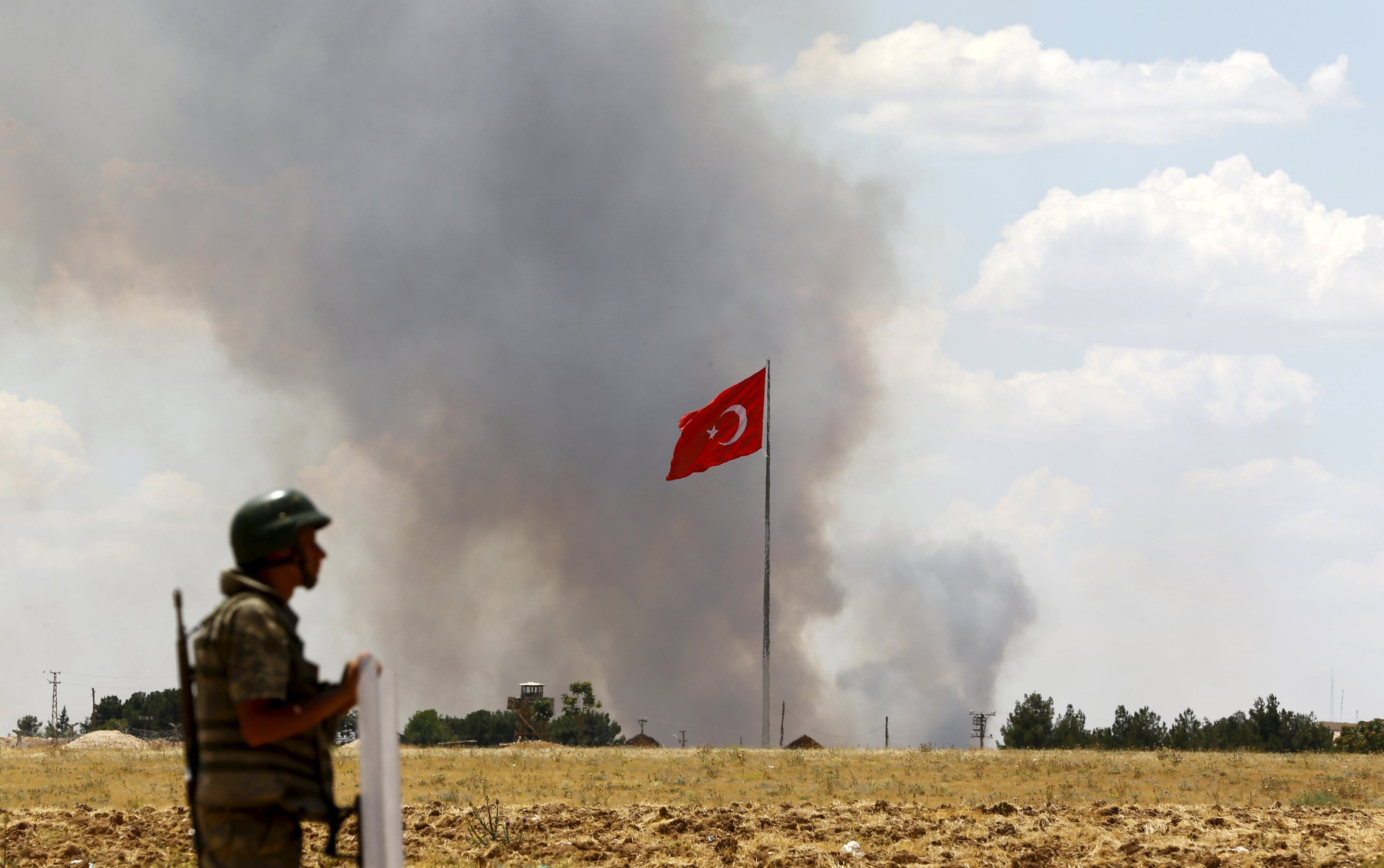 A Turkish soldier stands guard while smoke rises in the Syrian town of Kobane as it is seen from the Turkish border town of Suruc. (File: Reuters)
