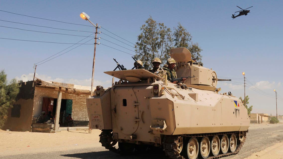 In this Tuesday, May 12, 2013 file photo, Egyptian Army soldiers patrol in an armored vehicle backed by a helicopter gunship during a sweep through villages in Sheikh Zuweyid, north Sinai, Egypt. AP