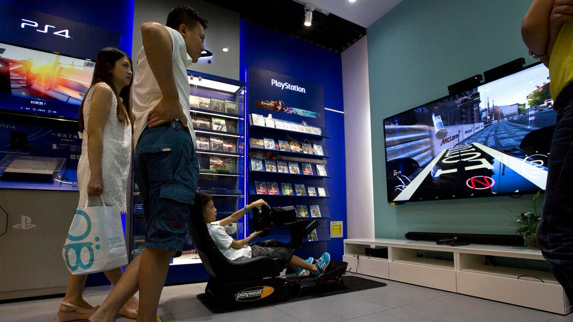 A child tries out a video game at a shop in Beijing, Monday, July 27, 2015. China is lifting its ban on sales of video game consoles to promote the industry and a new manufacturing zone in Shanghai. (AP)