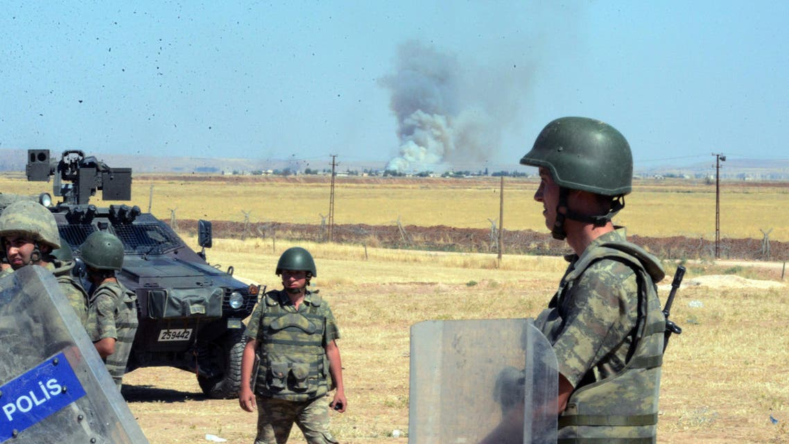 Turkish soldiers stand as smoke billows from the Syrian town of Ayn al-Arab, or Kobani, following the attacks by IS militants as seen from the Turkish side of the border in Suruc, Turkey, Thursday, June 25, 2015. AP