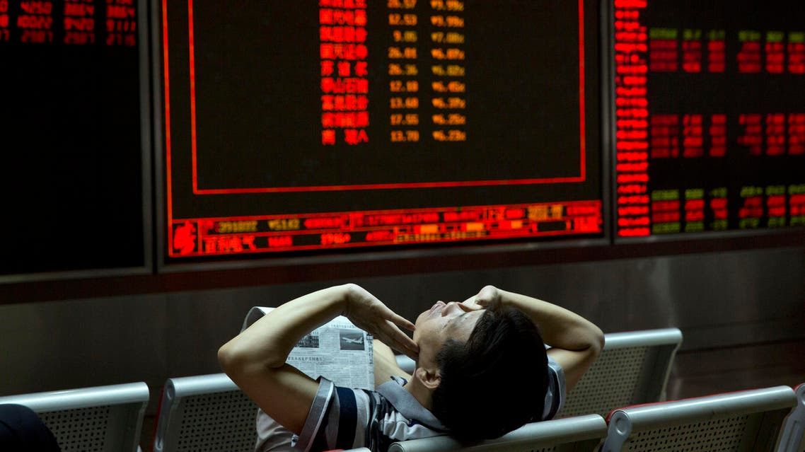 An investor stretches as he takes a break from monitoring stock prices at a brokerage in Beijing Tuesday, July 14, 2015. AP