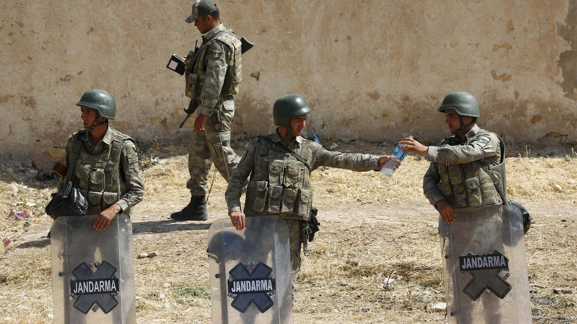 Turkish soldier shares a bottle of water with his comrade as they stand guard near the Mursitpinar border gate in Suruc, bordering with Syrian town of Kobani, Sanliurfa province, Turkey. R