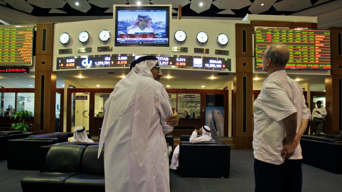 Emirati and other traders discuss the latest news at the Dubai Financial Market in Dubai, United Arab Emirates, Tuesday Aug. 9, 2011. AP
