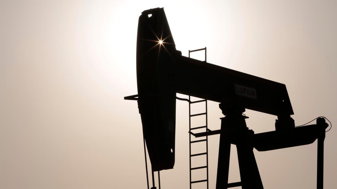 An oil pump works at sunset Thursday, July 16, 2015, in the desert oil fields of Sakhir, Bahrain. AP