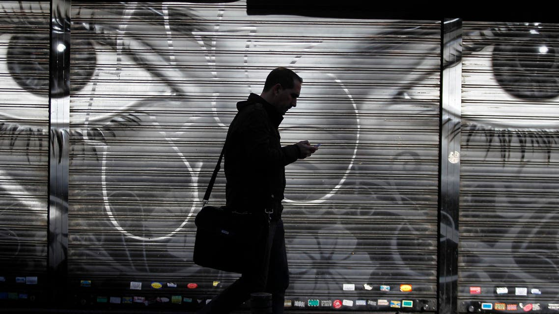 A man looks at his cell phone as he walks on the street in downtown Madrid, Thursday, Oct. 31, 2013. AP