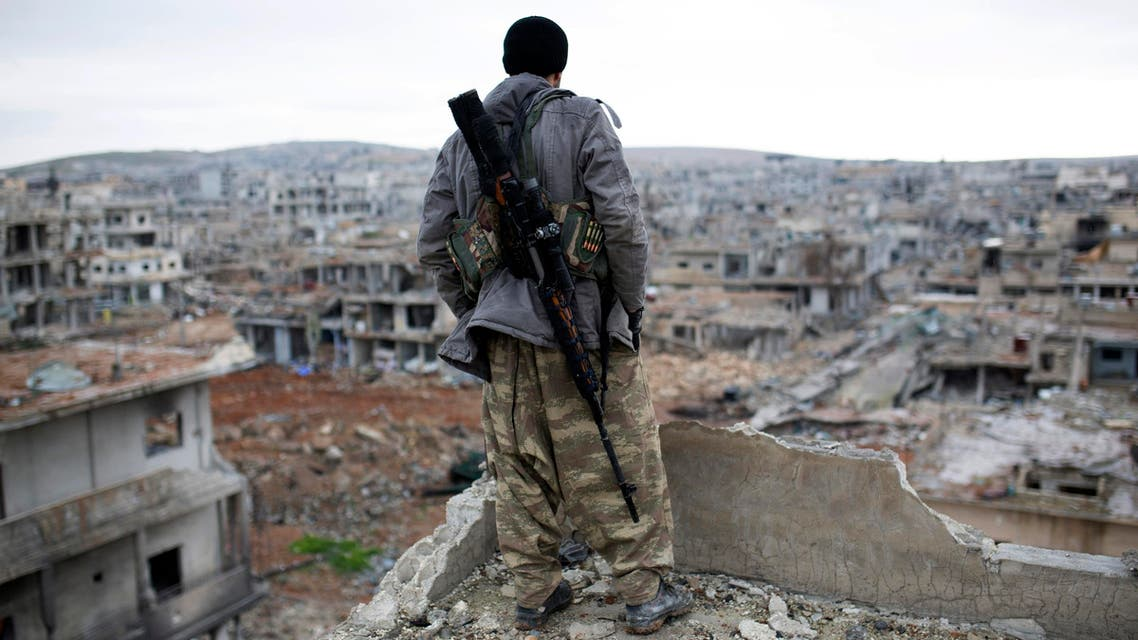 n this Jan. 30, 2015, file photo, a Syrian Kurdish sniper looks at the rubble in the Syrian city of Ain al-Arab, also known as Kobani. AP