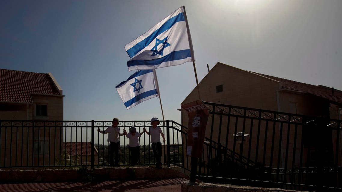 In this Sunday, April 22, 2012 file photo, Israeli flags fly over the Ulpana neighborhood in the West Bank settlement of Beit El near Ramallah. (AP)