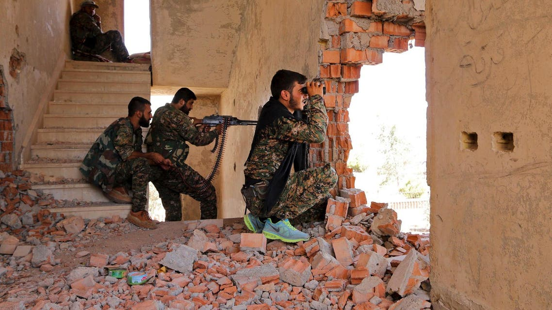 Kurdish People's Protection Units fighters take up positions inside a damaged building in al-Vilat al-Homor, as they monitor the movements of ISIS fighters who are stationed in Ghwayran. (Reuters)