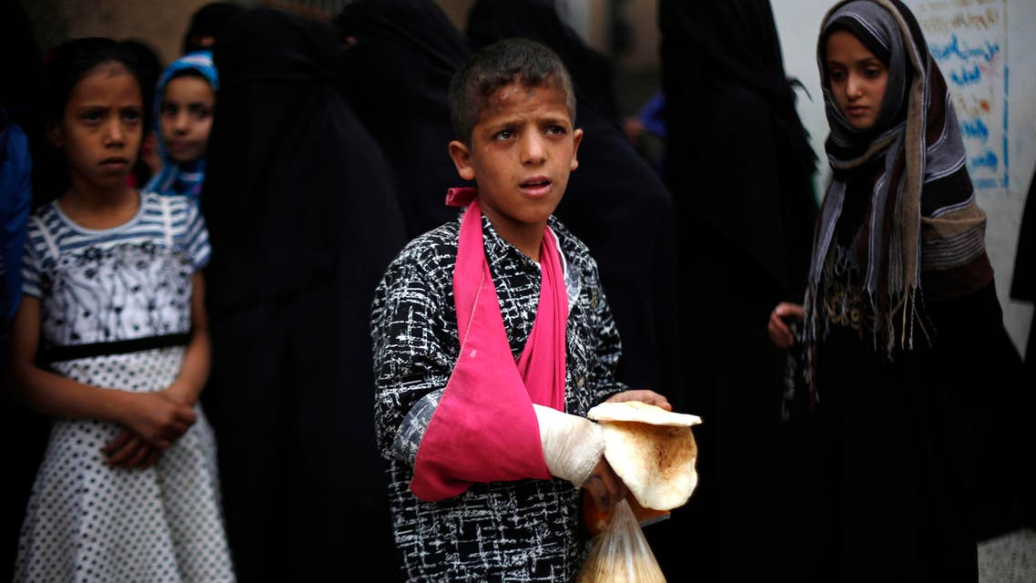 A Yemeni boy stands after receiving free food donated by Yemeni volunteers during the holy month of Ramadan, in Sanaa, Yemen, Friday, June 26, 2015. AP