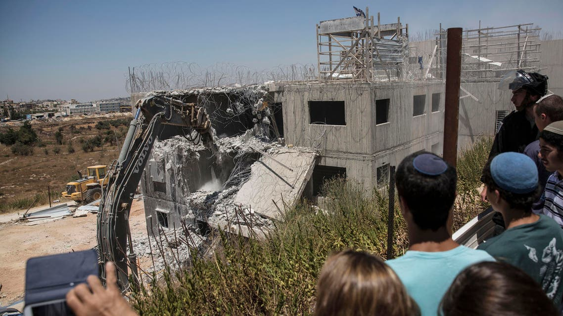 Young Israeli settlers watch the demolition of a building at the Jewish settlement of Beit El, near the West Bank town of Ramallah, Wednesday, July 29, 2015. AP