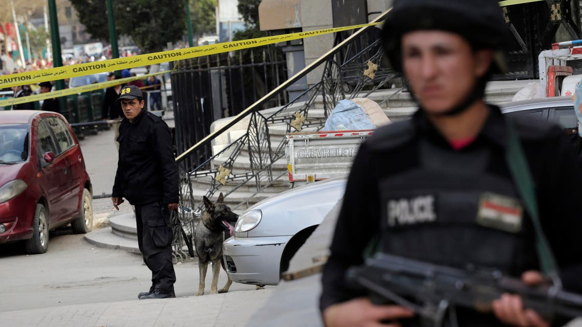 An Egyptian policeman stands alert as another member of bomb squad handle a sniffer dog after a bomb blast near the Egyptian High Court, in downtown Cairo, Egypt, Monday, March 2, 2015.  AP