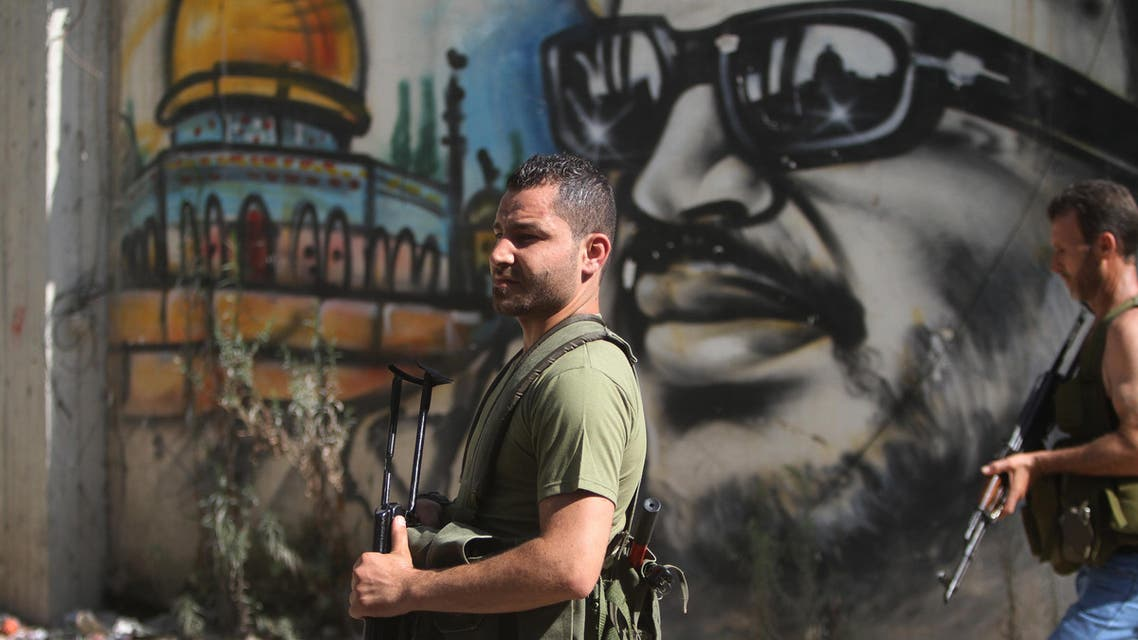 Palestinian gunmen from the Fatah movement, hold their weapons as they walk in front of graffiti of late Palestinian leader Yasser Arafat, at Ein el-Hilweh Palestinan refugee camp, in the southern port city of Sidon, Lebanon, Staurday, July 25, 2015. AP