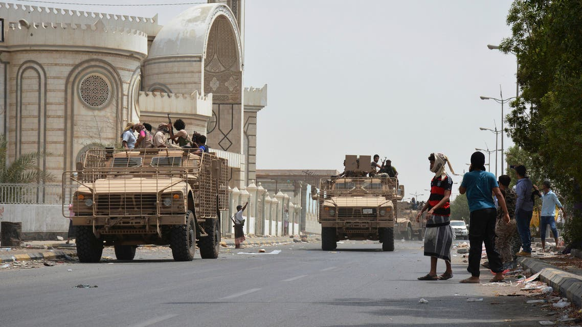 People watch fighters against Shiite rebels as they ride military vehicles on a street in the port city of Aden, Yemen, Tuesday, July 14, 2015. AP