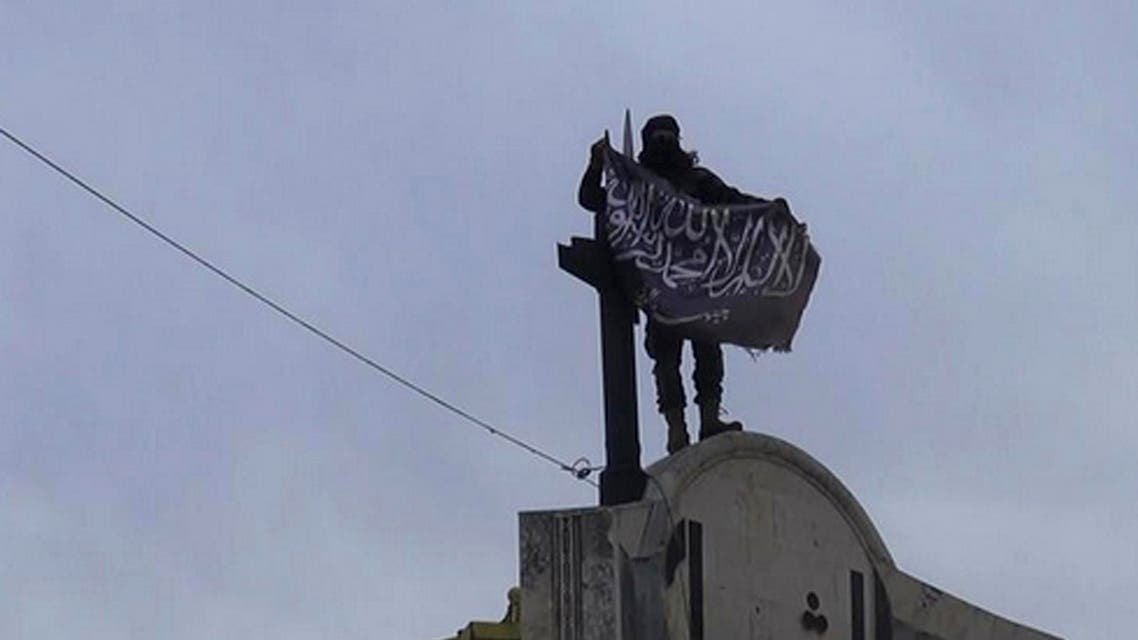 FILE - In this file photo posted on the Twitter page of Syria's al-Qaida-linked Nusra Front on Saturday, March 28, 2015, which is consistent with AP reporting, a fighter from Syria's al-Qaida-linked Nusra Front holds his group flag in Idlib province, north Syria. In the span of a month, a coalition of Syrian insurgents has routed government forces across the country's northwest, flushing them out of strongholds in a string of embarrassing loses for President Bashar Assad. (Al-Nusra Front Twitter page via AP, File)