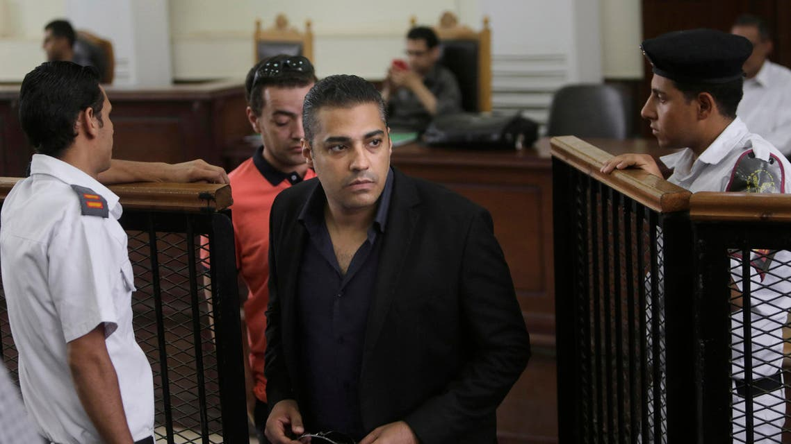 Policemen accompany Canadian Al-Jazeera English journalist Mohammed Fahmy, during their retrial at a courtroom, in Tora prison, in Cairo, Egypt, Thursday, June 25, 2015. Fahmy is being tried along with Egyptian producer Baher Mohammed on charges accusing them of being part of a terrorist group and airing falsified footage intended to damage national security. The retrial in a case widely criticized by human rights organizations and media groups has been postponed to June 29. (AP Photo/Amr Nabil)