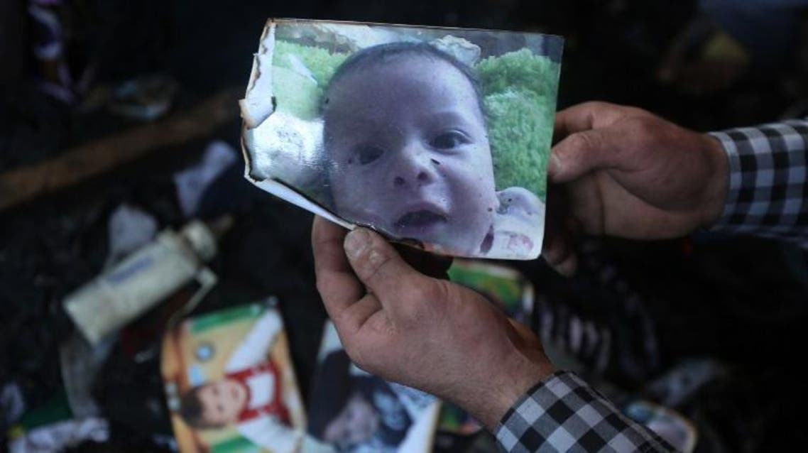 A man shows a picture of 18-month-old Palestinian toddler Ali Saad Dawabsha who died when his family house was set on fire by alleged Jewish extremists in the West Bank village of Duma. (AFP)