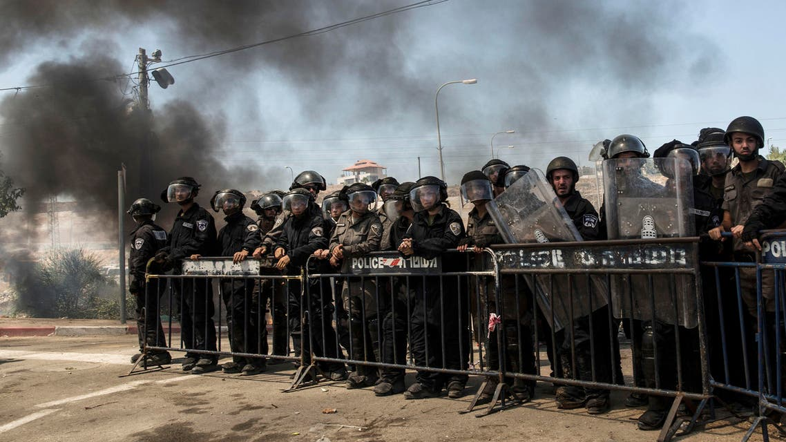 Israeli police stand by with riot gear, during the demolition of a building at the Jewish settlement of Beit El, near the West Bank town of Ramallah, Wednesday, July 29, 2015. (AP)