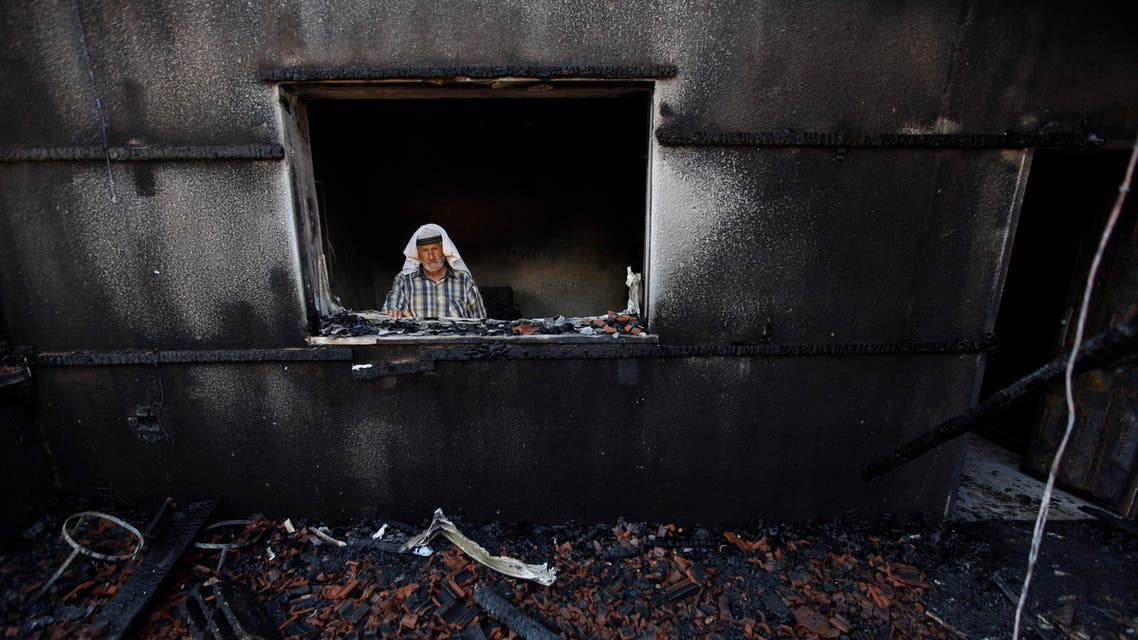 A Palestinian man inspects a house after it was torched in a suspected attack by Jewish settlers killing an 18-month-old Palestinian child. (AP)