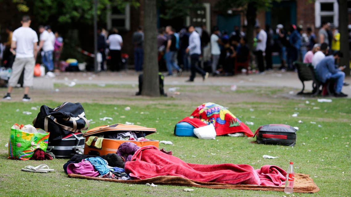 Two children sleep on the ground near their belongings in front of the reception center for refugees in Berlin, Germany, Wednesday, July 22, 2015. Figures released last week showed that about 180,000 asylum applications were filed in the first six months of 2015, more than twice as many as in the same period last year. (AP Photo/Markus Schreiber)