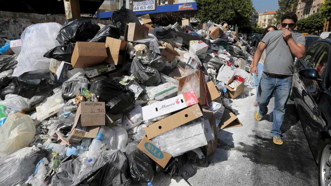 A man covers his nose as he walks past a pile of garbage along a street in Beirut, Lebanon July 22, 2015. (Reuters)