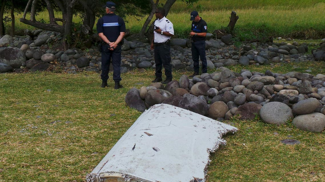 French gendarmes and police stand near a large piece of plane debris which was found on the beach in Saint-Andre, on the French Indian Ocean island of La Reunion. (Reuters)