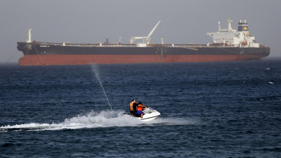 "A couple rides a jetski past the Egyptian crude oil tanker ""Sharifa 4"" near the beach in El Ain El Sokhna port in Suez before the tanker enters the Suez Canal, east of Cairo, Egypt, July 26, 2015. The first cargo ships passed through Egypt's New Suez Canal on Saturday in a test-run before it opens next month, state media reported, 11 months after the army began constructing the $8 billion canal alongside the existing 145-year-old Suez Canal. REUTERS/Amr Abdallah Dalsh"