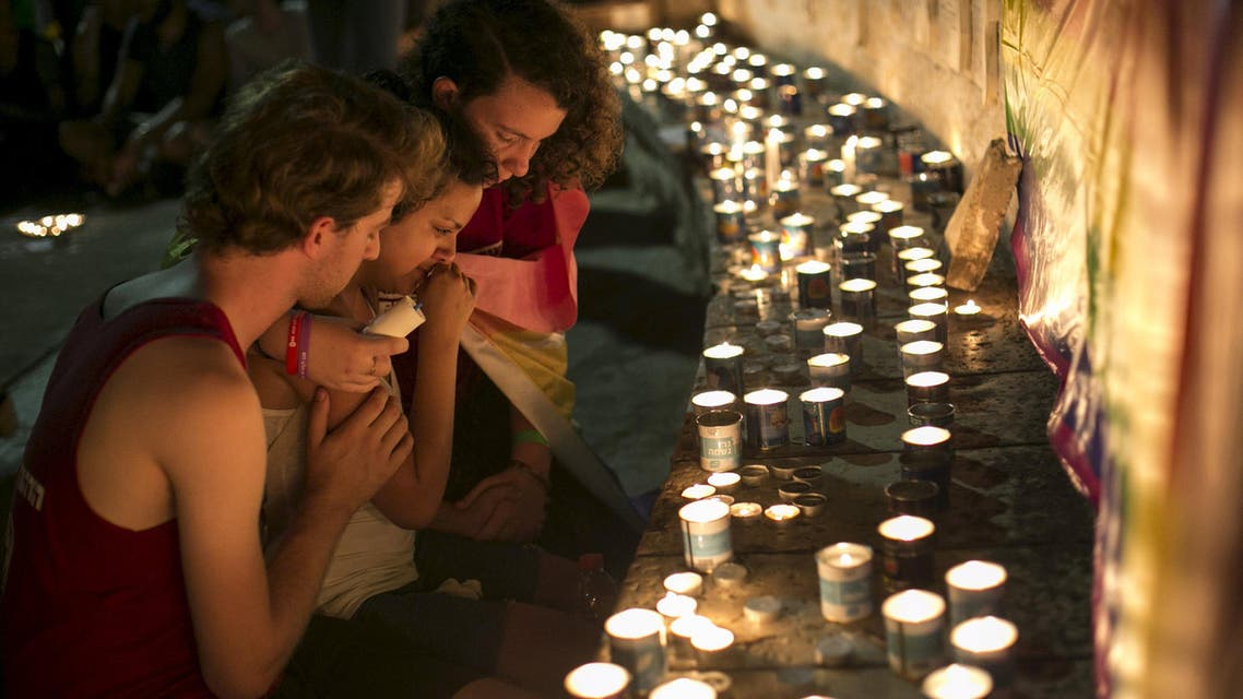 Israeli youths sit next to candles during a candlelight vigil in Tel Aviv, Israel, for Shira Banki, who died on Sunday of stab wounds at a Gay Pride parade in Jerusalem three days ago, August 2, 2015. (Reuters)