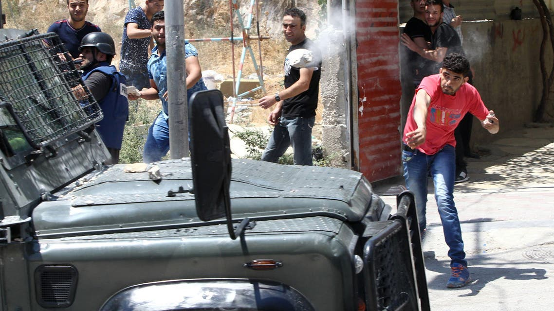 A Palestinian throws a stone towards a vehicle of Israeli security forces during clashes following a demonstration of Islamist Hamas supporters in support of Jerusalem's Al-Aqsa mosque on July 31, 2015 AFP