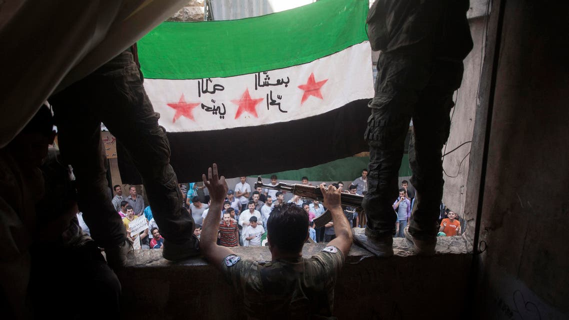 In this Friday, Sept. 21, 2012 file photo, Free Syrian Army rebels hold a revolutionary flag during a demonstration in the Bustan al-Qasr neighborhood of Aleppo, Syria. AP