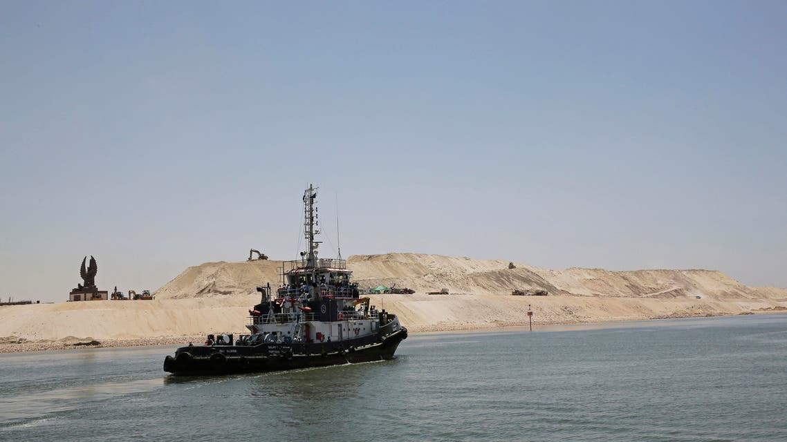 A boat passes through the new section of the Suez Canal during a media tour in Ismailia, Egypt, Wednesday, July 29, 2015.