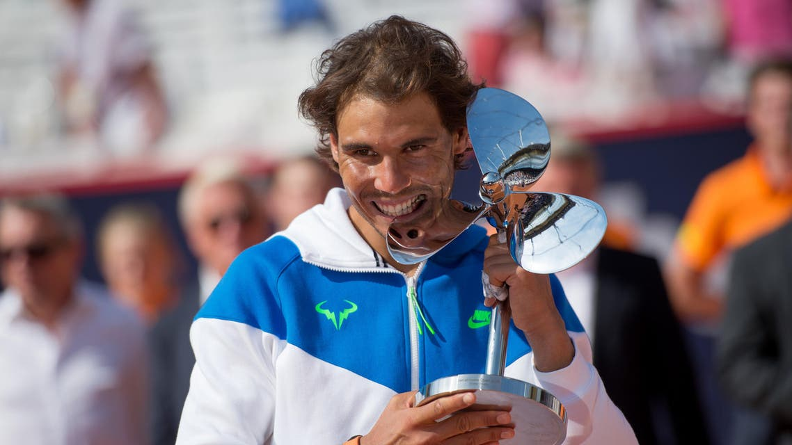 Spain's Rafael Nadal celebrates with the trophy after he won the final match of the Hamburg Open ATP tennis tournament against Fabio Fognini of Italy, in Hamburg, Germany, Sunday Aug. 2, 2015. AP