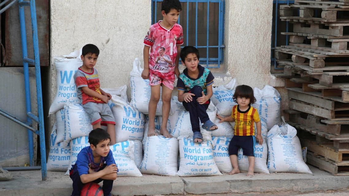 In this Friday, June 19, 2015 file photo, children sit on bags of rice from the World Food Programme at a school that serves as a shelter for internally displaced people in Baghdad's eastern district of Jamila, Iraq. The number of people displaced within Iraq due to violence and fighting by the Islamic State group has exceeded 3 million, the United Nations said Tuesday, June 23, a grim milestone for the war-battered country. (AP Photo/Karim Kadim, File)
