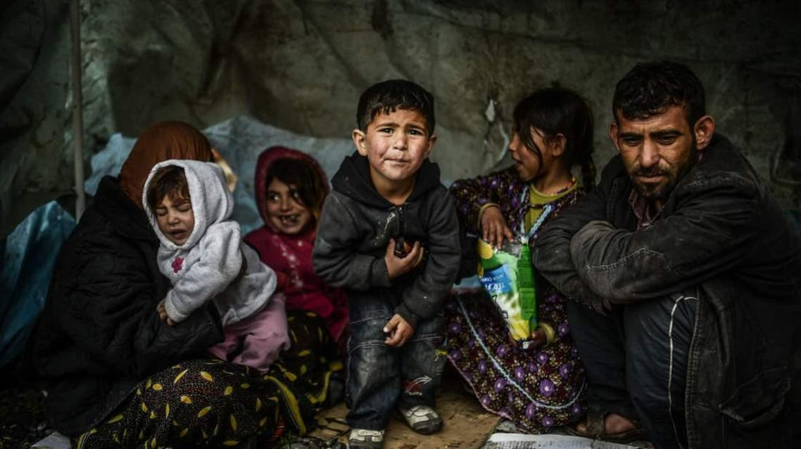 A Syrian refugee family from Aleppo stays under a shelter during a rainy day on March 8, 2014 in Uskudar, Istanbul. (AFP)