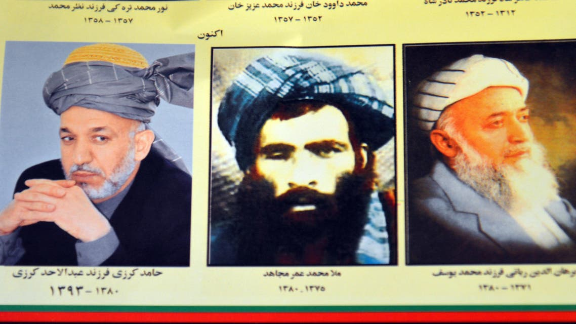 In this Thursday, July 30, 2015. file photo, an Afghan shop clerk shows a calendar with pictures of Afghan leaders including Mullah Mohammad Omar, center, in Kandahar, south of Kabul, Afghanistan. (AP)