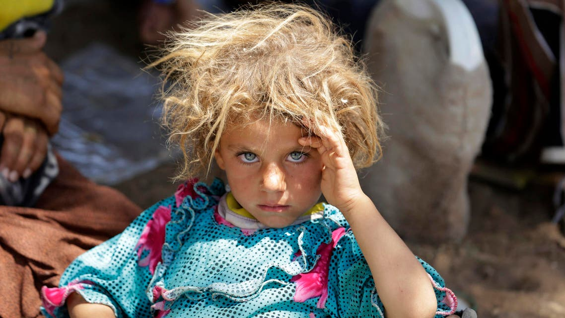 A girl from the minority Yazidi sect, fleeing the violence in the Iraqi town of Sinjar, rests at the Iraqi-Syrian border crossing in Fishkhabour, Dohuk province August 13, 2014. (Reuters)