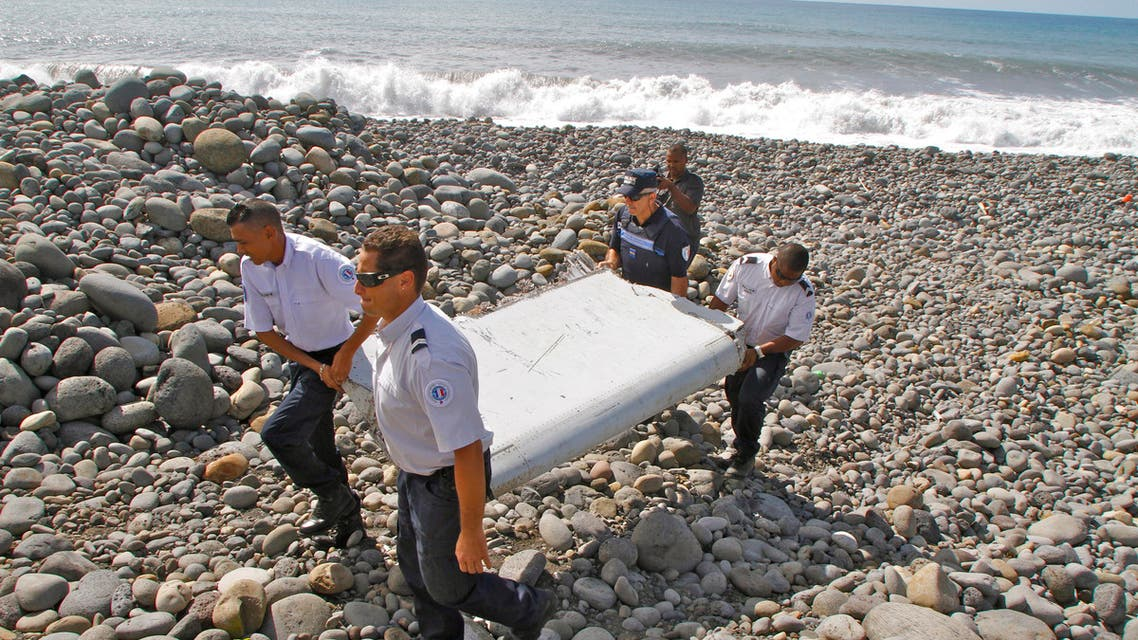 """In this photo dated Wednesday, July 29, 2015, French police officers carry a piece of debris from a plane in Saint-Andre, Reunion Island. Air safety investigators, one of them a Boeing investigator, have identified the component as a """"flaperon"""" from the trailing edge of a Boeing 777 wing, a U.S. official said. Flight 370, which disappeared March 8, 2014, with 239 people on board, is the only 777 known to be missing. (AP Photo/Lucas Marie)"""