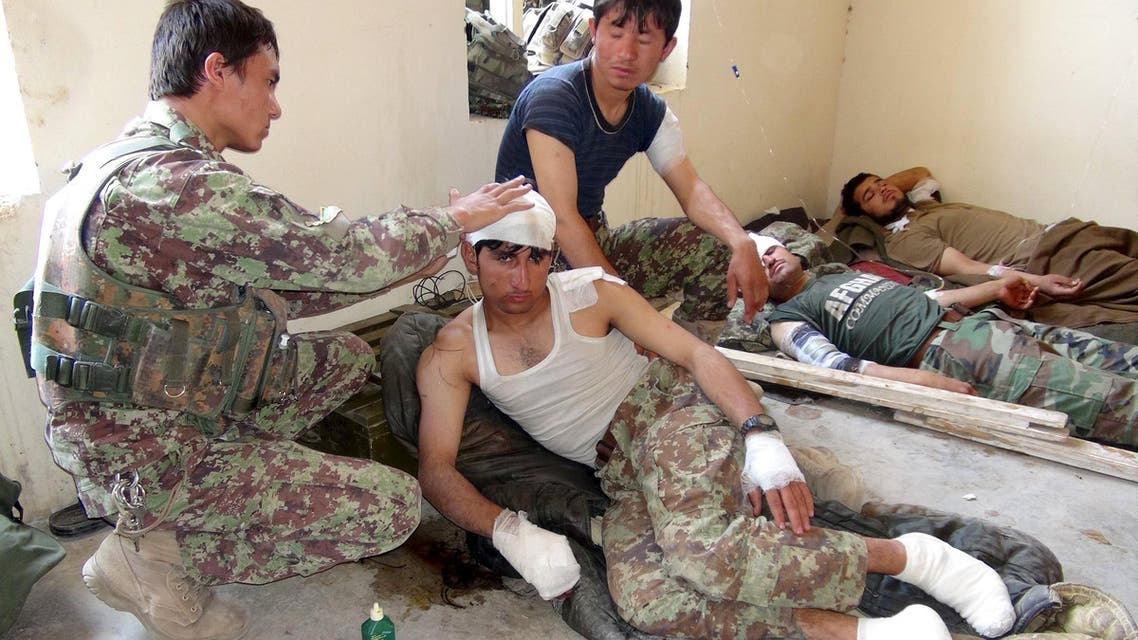 """A wounded Afghan soldier is treated after an air strike in Baraki Barak district of Logar province, Afghanistan July 20, 2015. At least eight Afghan soldiers were killed in a """"friendly fire"""" incident on Monday when NATO forces mistakenly launched an air strike on their army outpost in eastern Afghanistan, Afghan officials said. REUTERS/Stringer"""