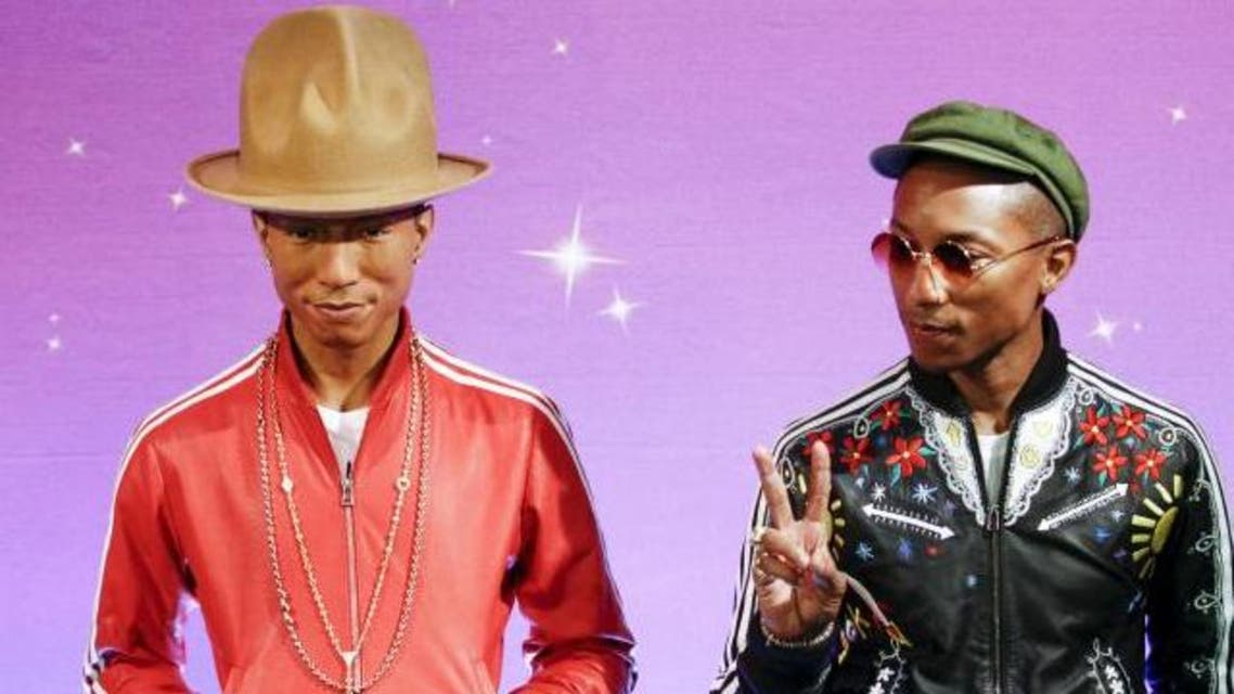 Musician Pharrell Williams makes peace symbol as he meets his wax double at Madame Tussauds in New York April 1, 2015. Reuters
