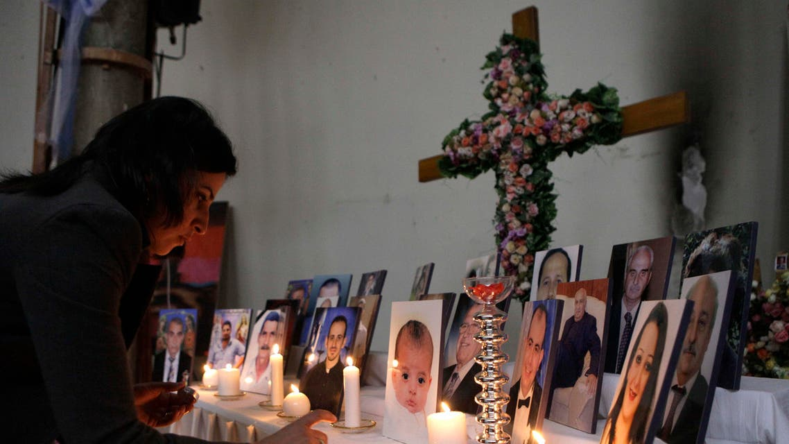A woman lights a candle among pictures of slain Iraqi Christians at Our Lady of Salvation church in Baghdad, Iraq, Friday, Dec. 31, 2010. Militants in Iraq have attacked at least four Christian homes with a combination of grenades and bombs, killing and wounding a few people and sending fear into the country's already terrified tiny Christian community, police said. (AP Photo/Khalid Mohammed)