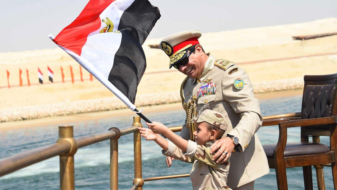 In this picture provided by the office of the Egyptian Presidency, Egyptian President Abdel-Fattah el-Sissi smiles at a boy dressed in a tiny military uniform as he waves the national flag from a monarchy-era yacht that sailed to the venue of a ceremony unveiling a major extension of the Suez Canal in Ismailia, Egypt, Thursday, Aug. 6, 2015. El-Sissi has billed the extension as an historic achievement needed to boost the country's ailing economy after years of unrest. (Egyptian Presidency via AP)