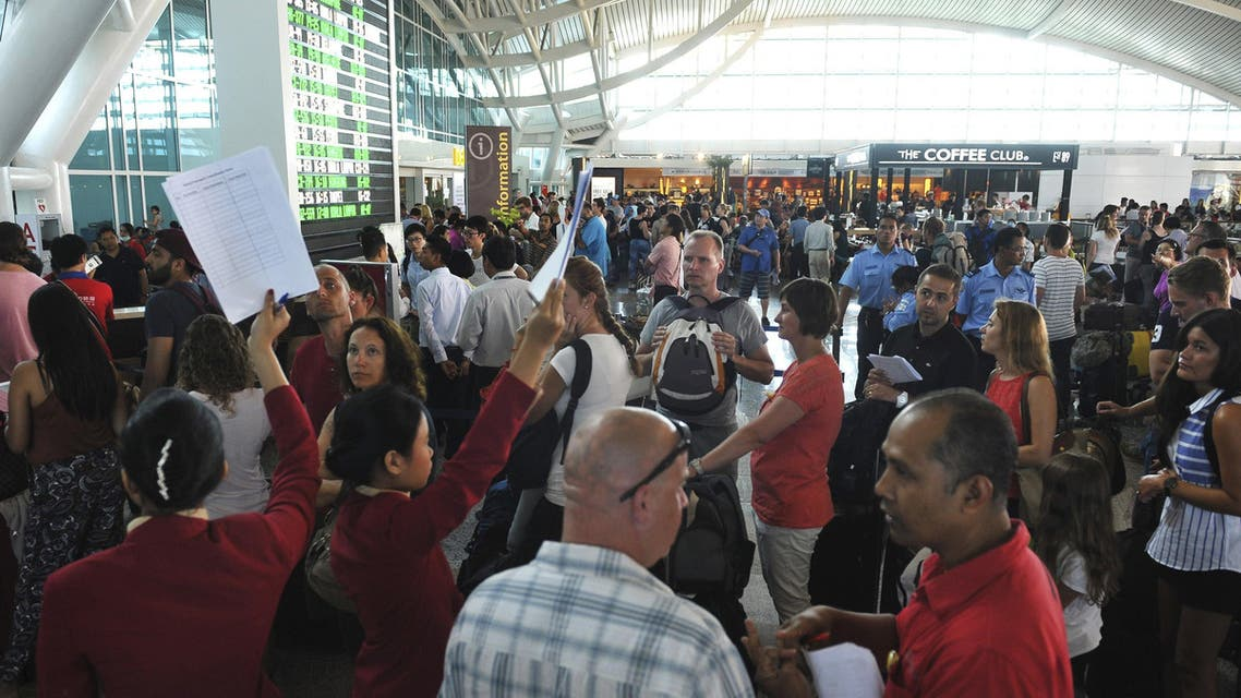 Passengers wait for information on their flights at the international departure terminal at Ngurah Rai Airport