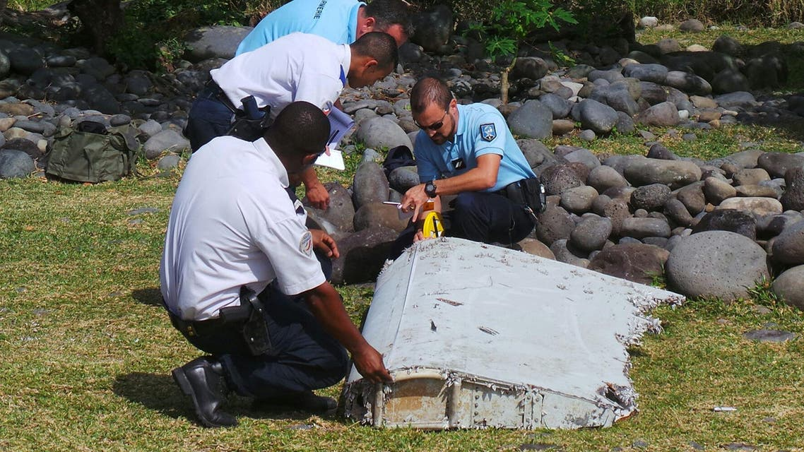 French gendarmes and police inspect a large piece of plane debris which was found on the beach in Saint-Andre, on the French Indian Ocean island of La Reunion, in this picture taken July 29, 2015. Investigators in France have ascertained that the barnacle-covered debris, a 2-2.5 metre (6.5-8 feet) wing surface known as a flaperon, belonged to Malaysia Airlines flight MH370 just days after Malaysia identified it as being part of the same model, a Boeing 777. Picture taken July 29, 2015. REUTERS/Zinfos974/Prisca Bigot/Files